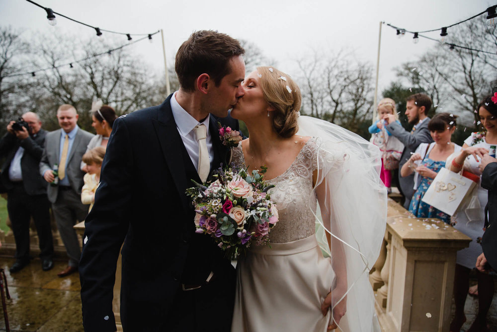 happily wedded couple share kiss on top of steps at Ashfield House