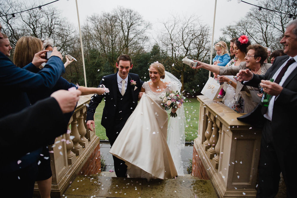 newlyweds walk up steps covered in confetti