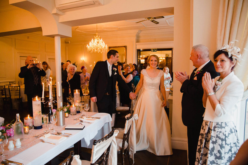 bride and groom entering wedding breakfast room for friends and family to celebrate
