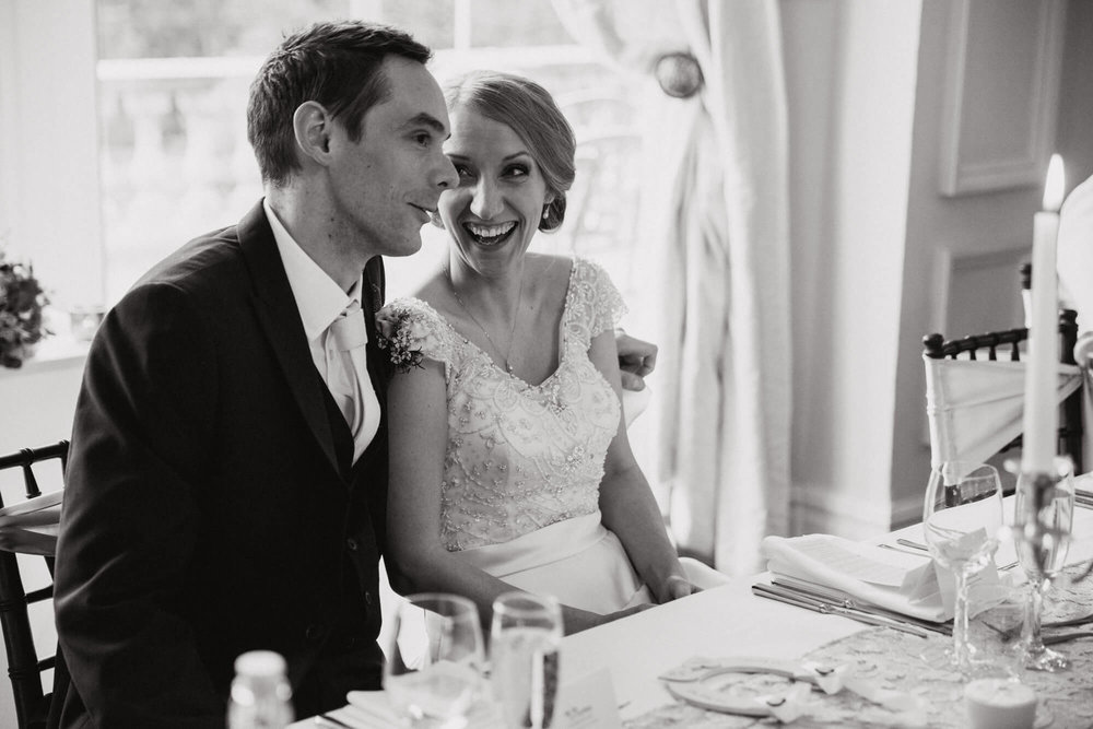 black and white photograph of bride laughing at groom on top table during speeches