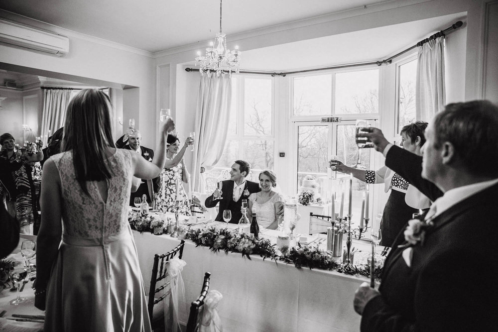 black and white photograph of friends and family all raising a toast to bride and groom