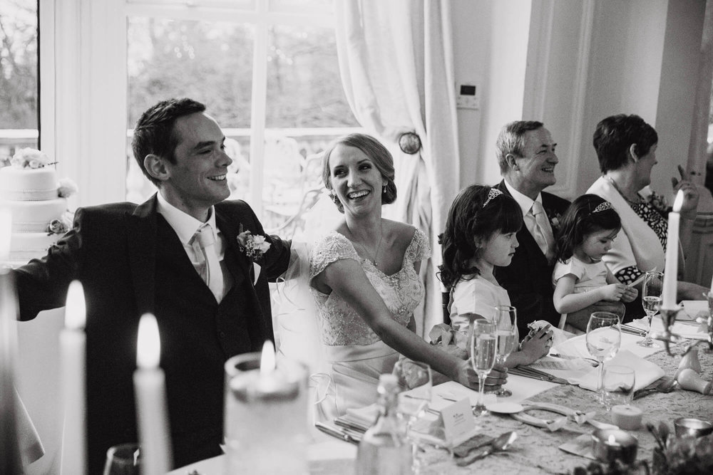 black and white photograph of bride laughing with groom during best mans speech