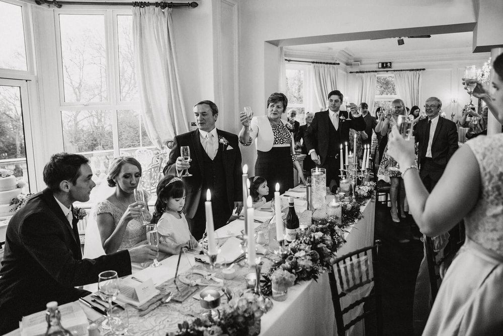 black and white photograph of wedding party raising glasses for newlyweds