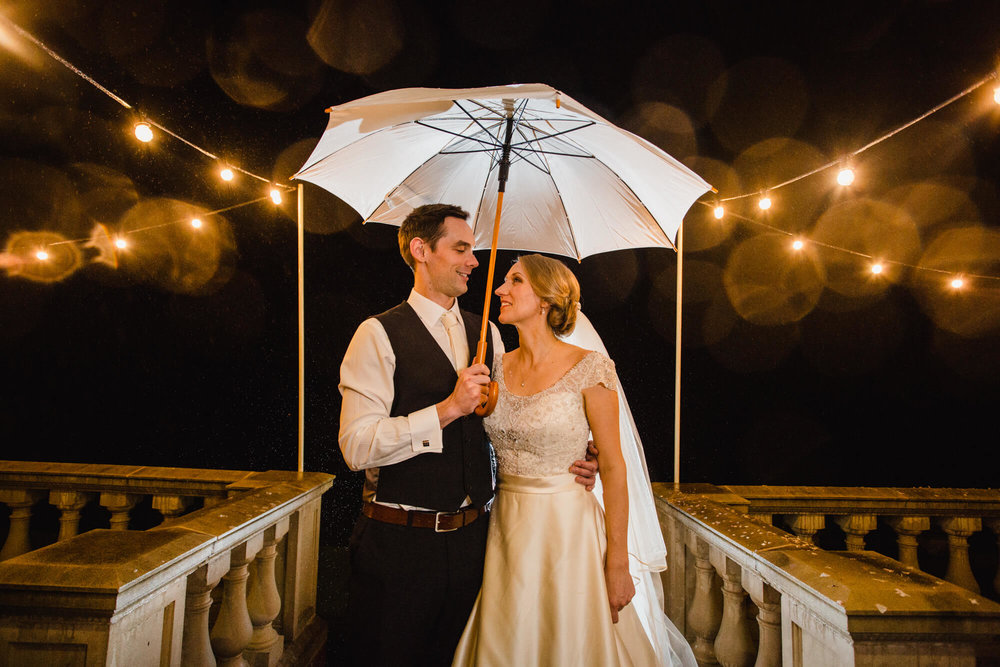 newlyweds under umbrella for nighttime portrait at Ashfield House