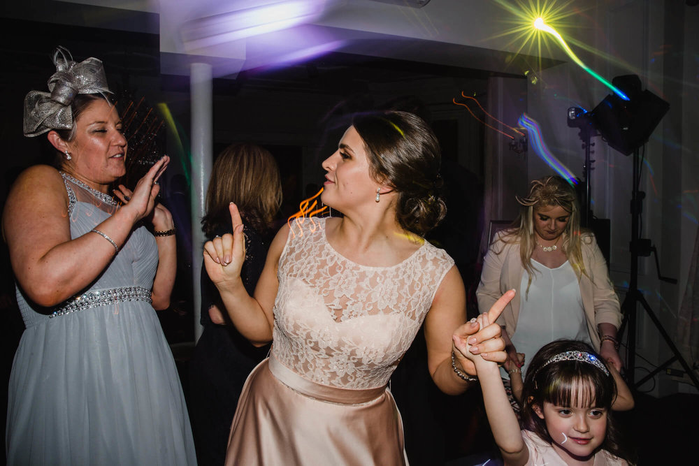 bridesmaid partying with guests on dancefloor