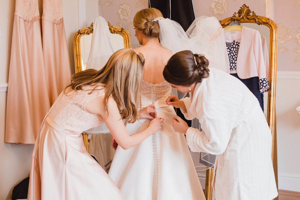 Bridesmaids fastening bridal dress before ceremony at Ashfield House