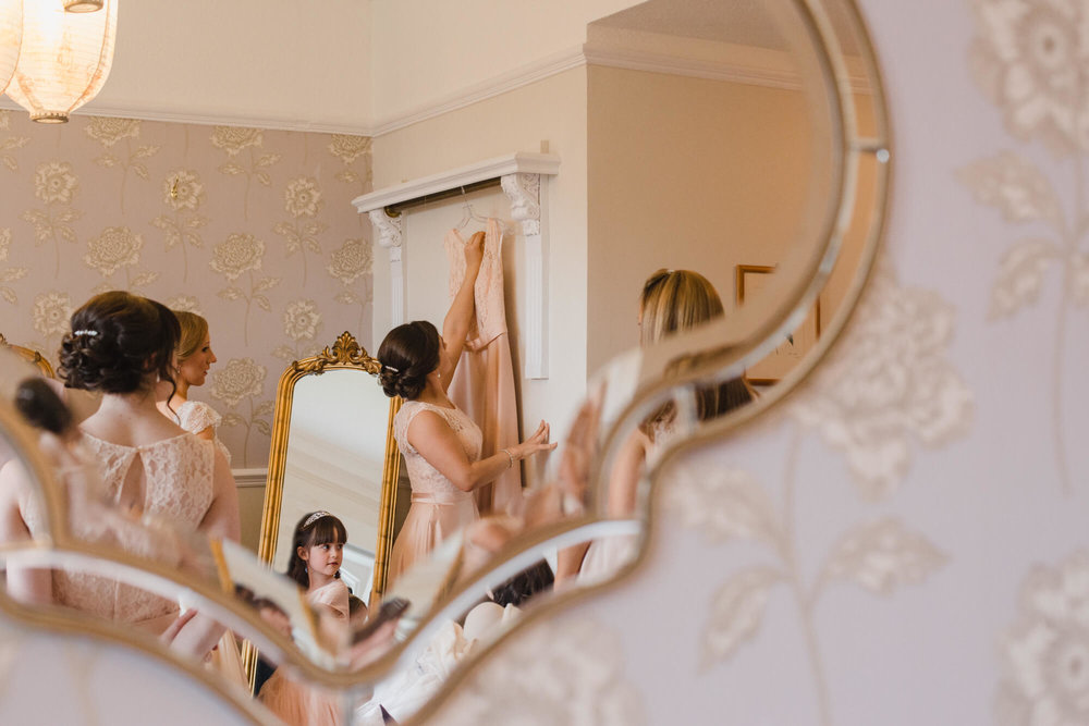 Photograph in the mirror reflection of bridesmaid hanging up her dress