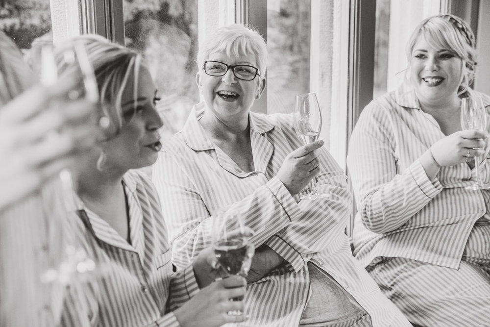 Black and white photograph of brides mother laughing at joke with bridesmaids