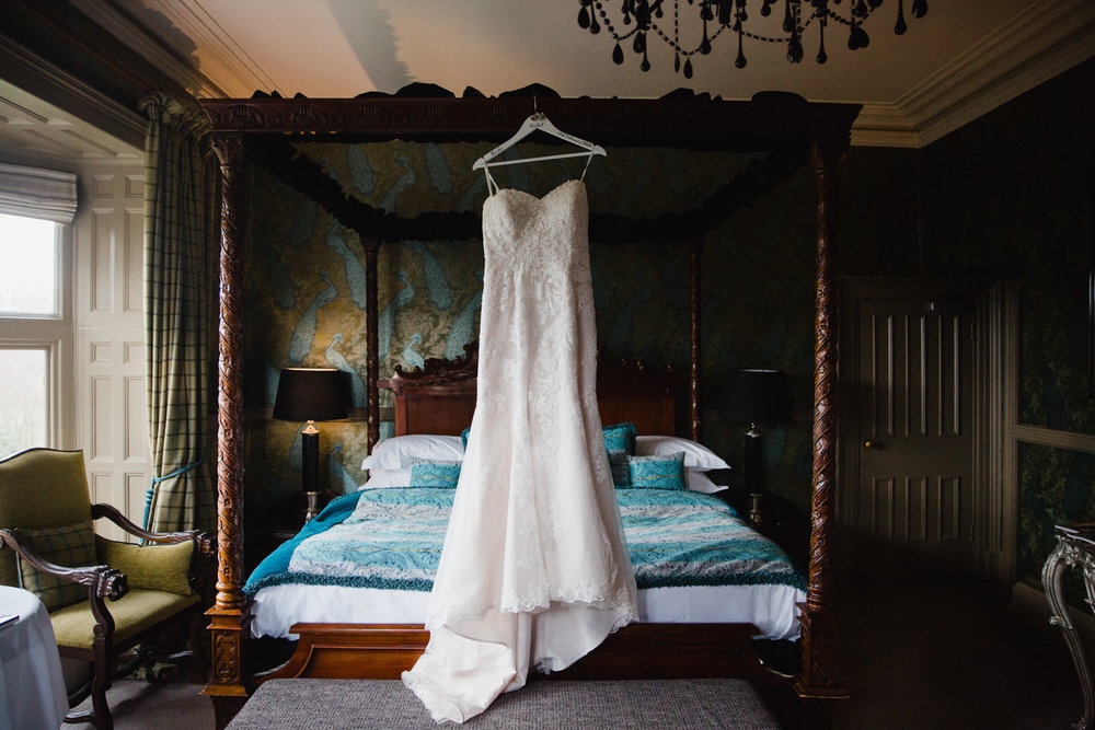 Sincerity Bridal wedding dress hanging on four poster bed at Mitton Hall