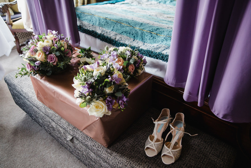 Wedding bouquets and shoes arranged in bridal suite with purple bridesmaid dresses