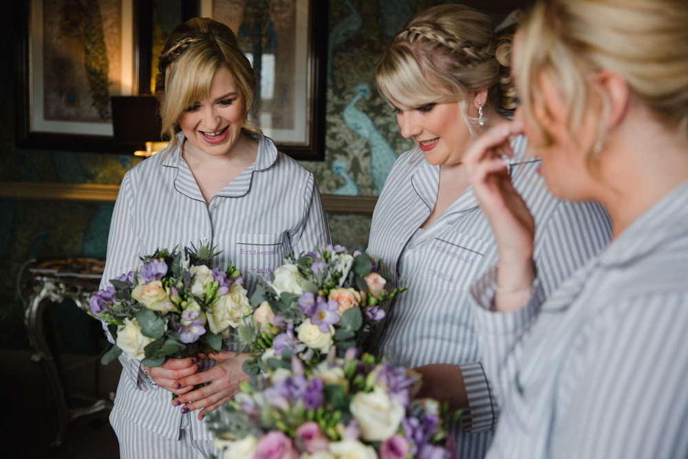 Bridesmaids smiling and laughing while holding Fizzy Fi lilac wedding bouquets