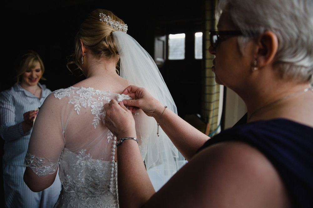 Close up photograph showing mother of bride fastening buttons on wedding dress
