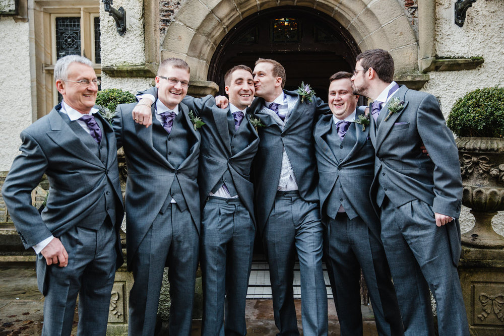 Groom and ushers in doorway pose for portrait photograph