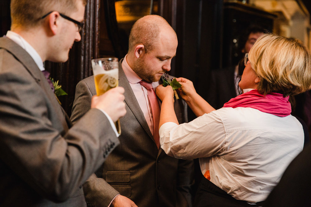 Best man has buttonhole fastened for service