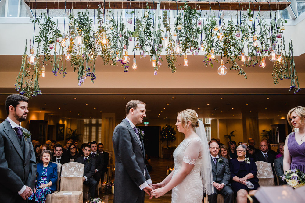 Bride and groom holding hands underneath typical type bespoke lighting