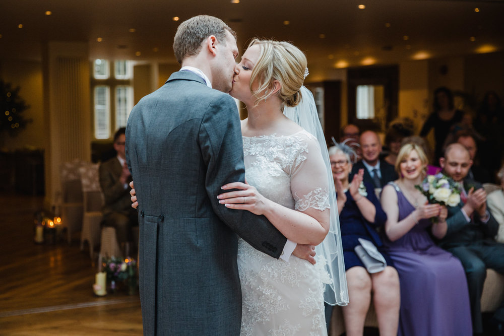 Close up photograph of bride and groom first kiss at Mitton Hall