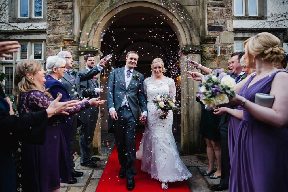 Photograph of guests throwing confetti at bride and groom