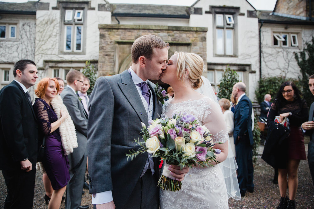 Newlyweds kiss after confetti with Mitton Hall backdrop