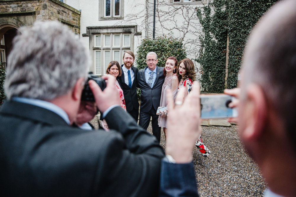 Wedding guests looking through their camera viewfinders for posed photograph