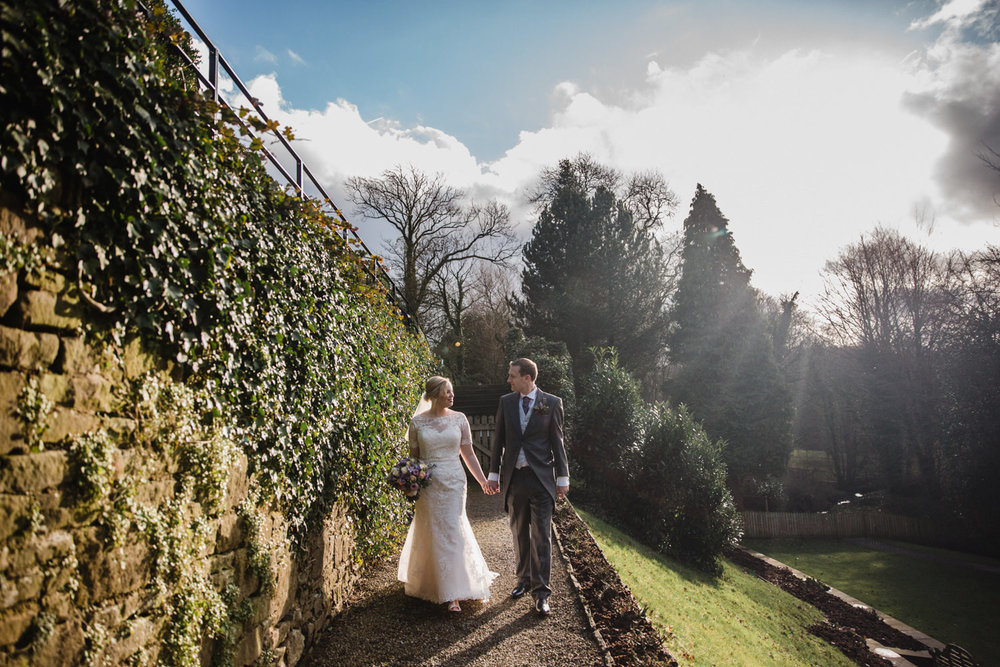 Newlyweds walk down path besides sun flare