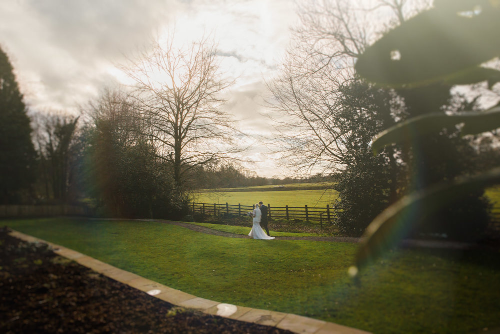 Lens flare photograph of couple walking in grounds at Mitton Hall
