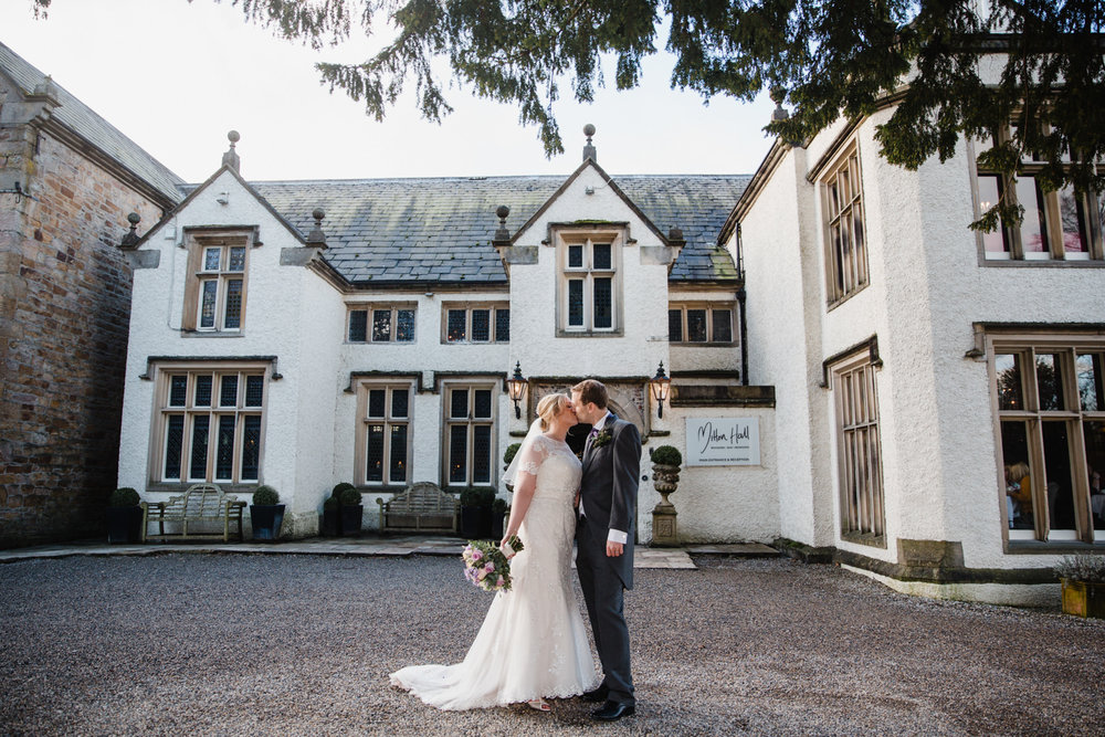 Newly wedded couple kissing in front of Mitton Hall entrance