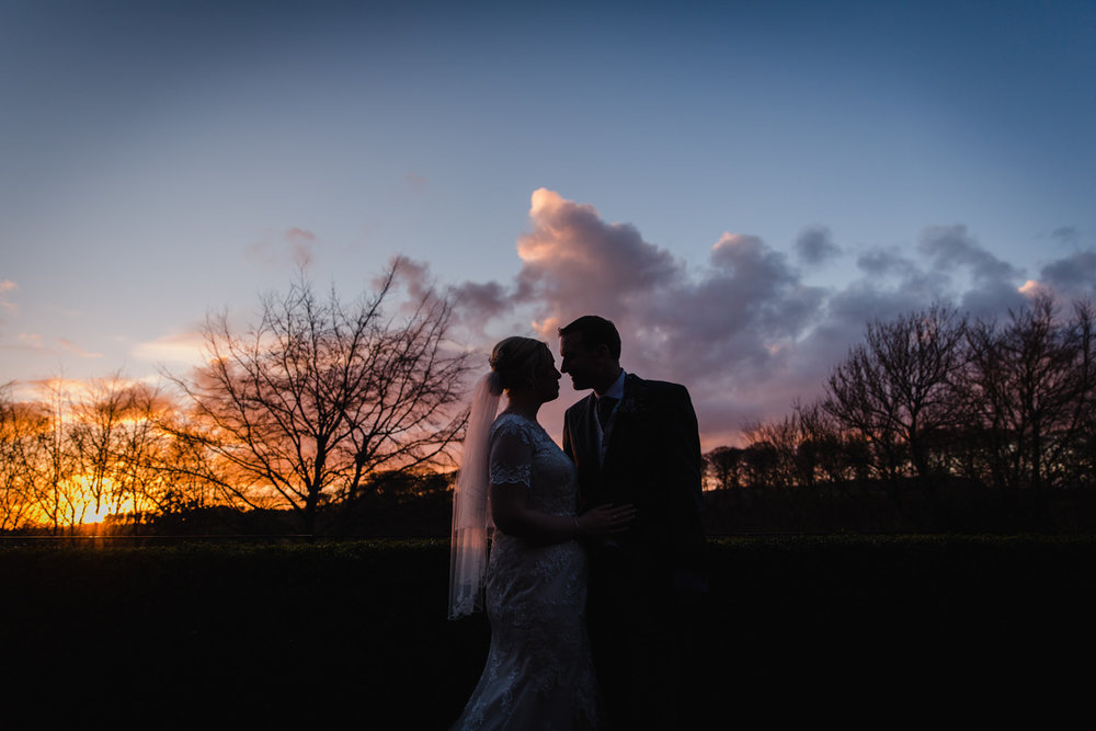 Under exposed silhouette sunset photograph of bride and groom