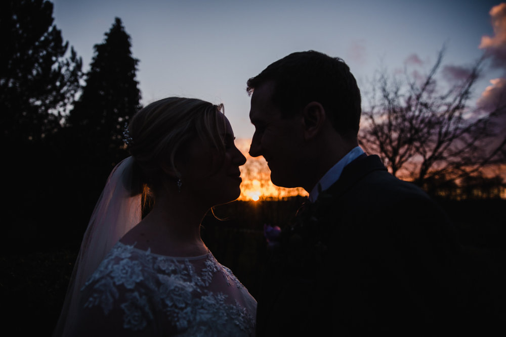 Close up of newlyweds sharing kiss with coloured sky exposure
