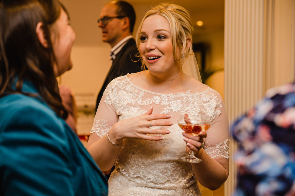 Bride sharing joke with wedding guest