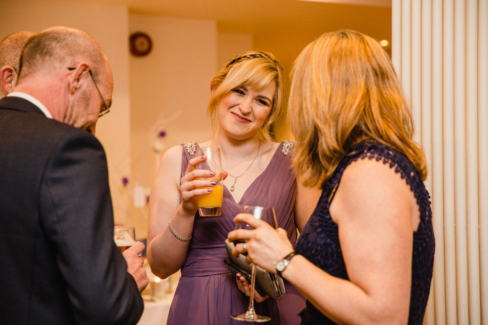 Bridesmaid laughing with guest after wedding service