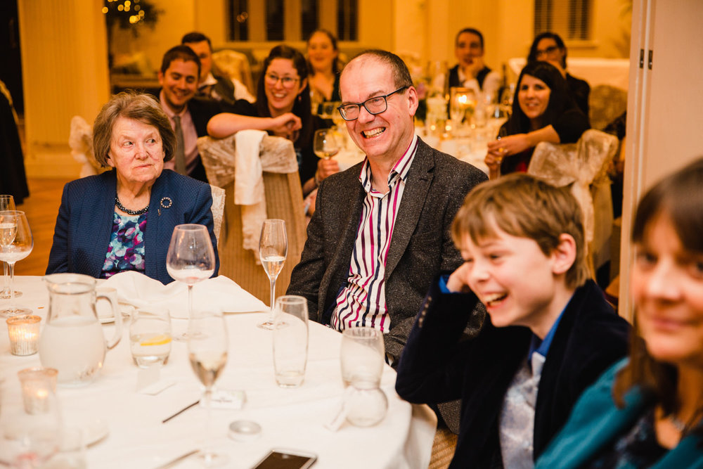 Candid moments and natural photograph of guests laughing at speeches
