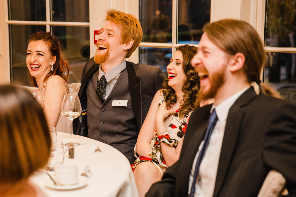 Table of guests all laughing together at wedding speeches