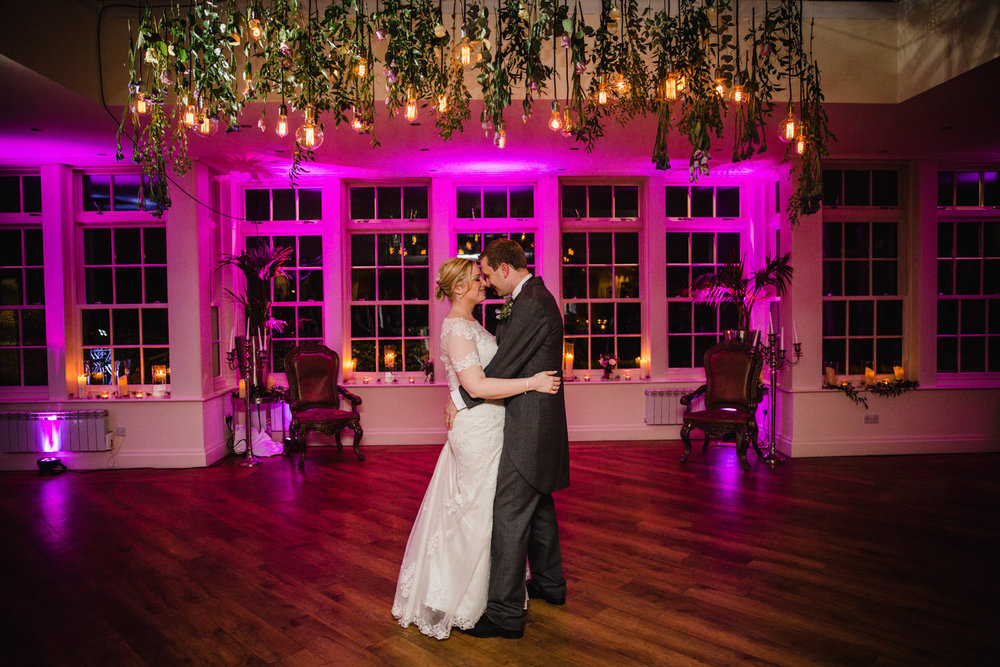 Newly married couple dancing under typical type bespoke wedding lighting