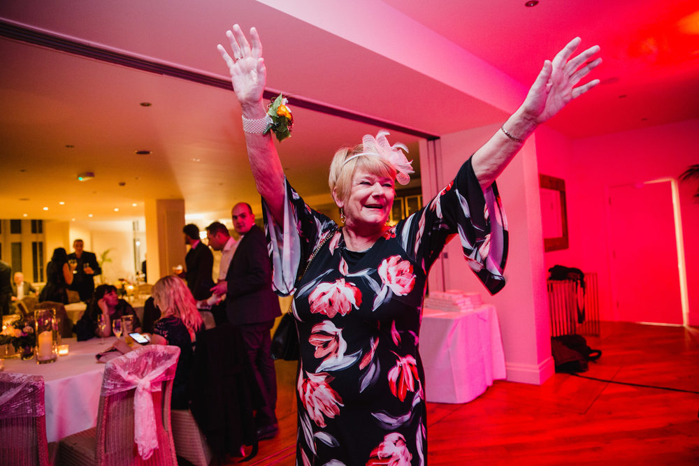 Wedding guest partying with arms up in the air