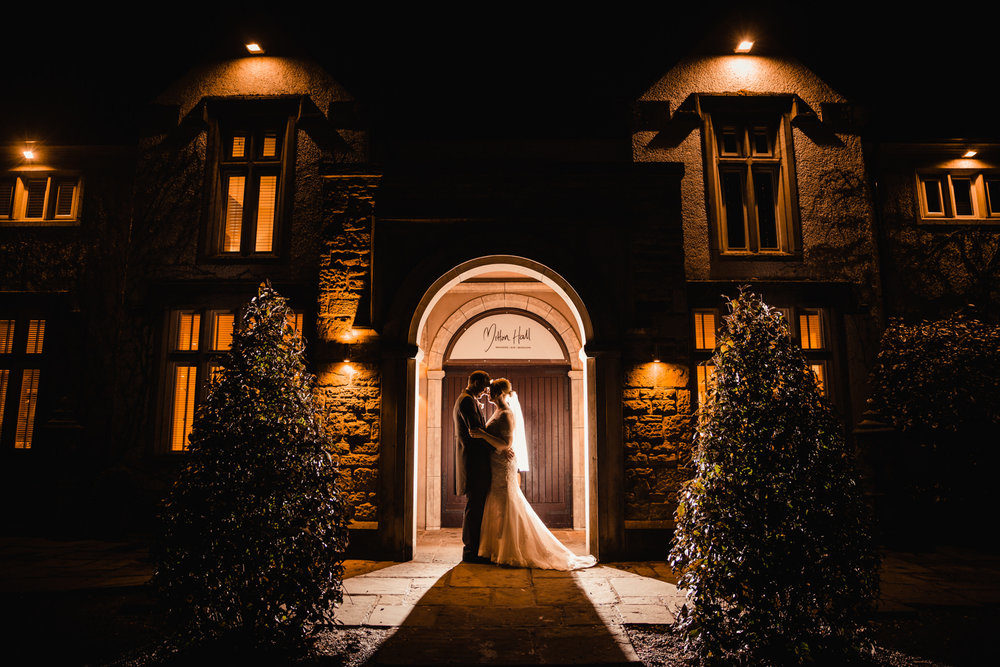 Copy of newlyweds flash lit in entrance way of Mitton Hall