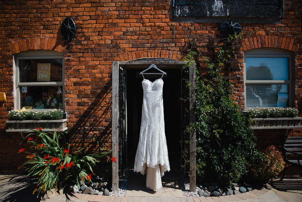 Wedding dress hung up in venue entrance