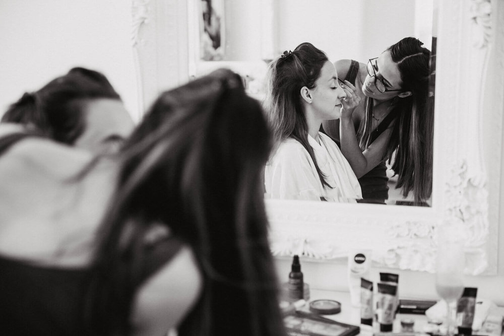 bride in mirror having make up applied