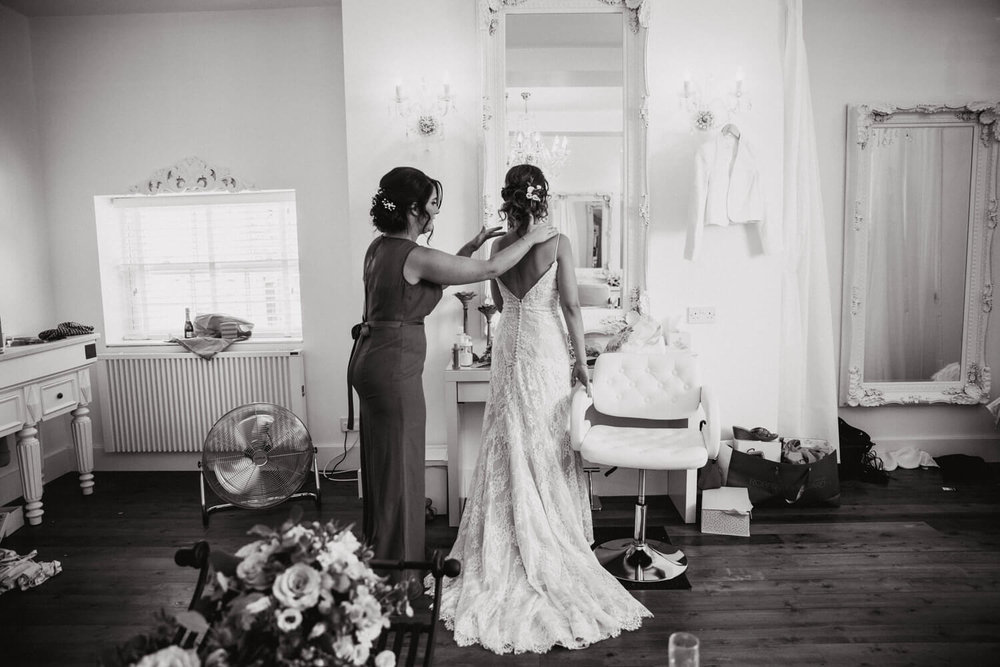 black and white photograph of bride looking in mirror being dressed by bridesmaid