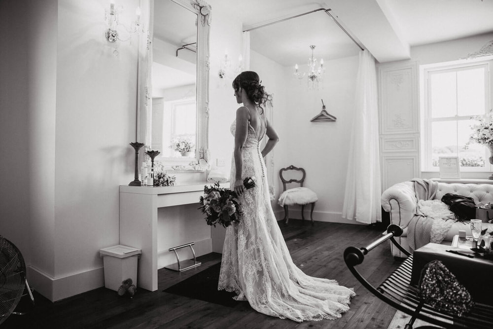 black and white photograph of bride in mirror holding bouquet