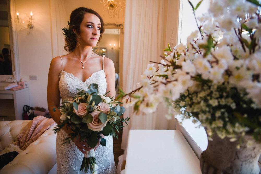 bride holding bouquet of flowers while looking out of window during wedding portrait