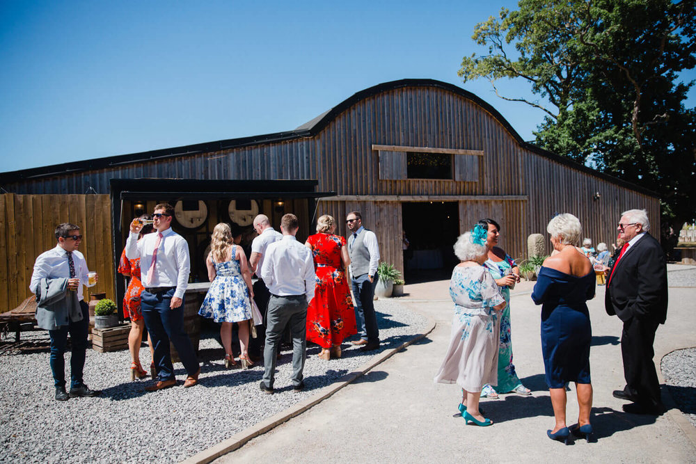 wedding guests having drinks outside of alcumlow wedding barn