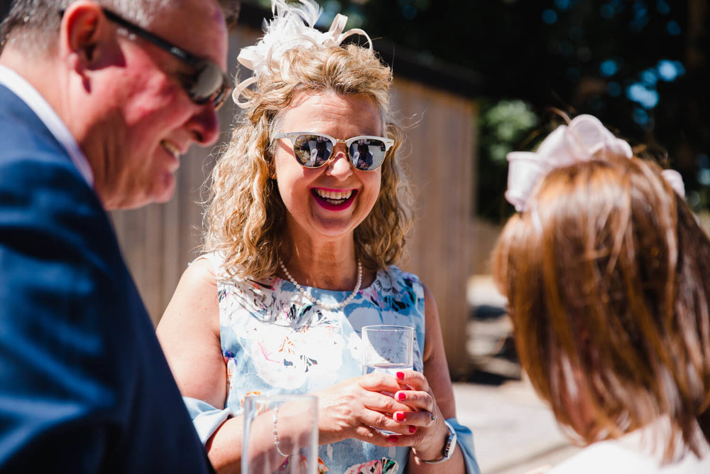 wedding guest in sunglasses laughing at joke