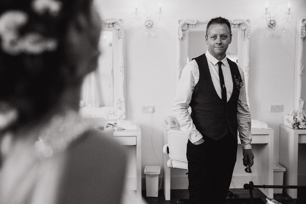 black and white photograph of father of bride looking on at daughter