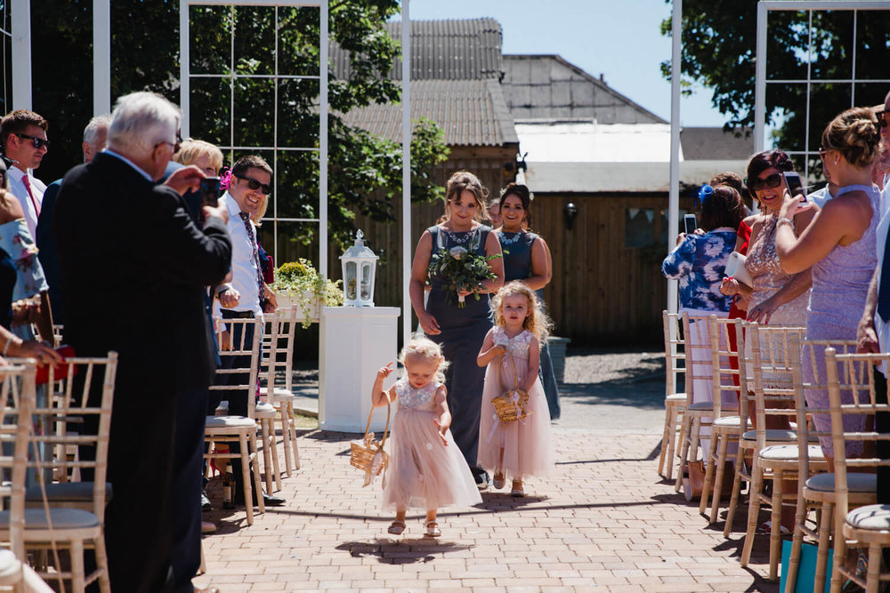 bridesmaids and flower girls running down aisle
