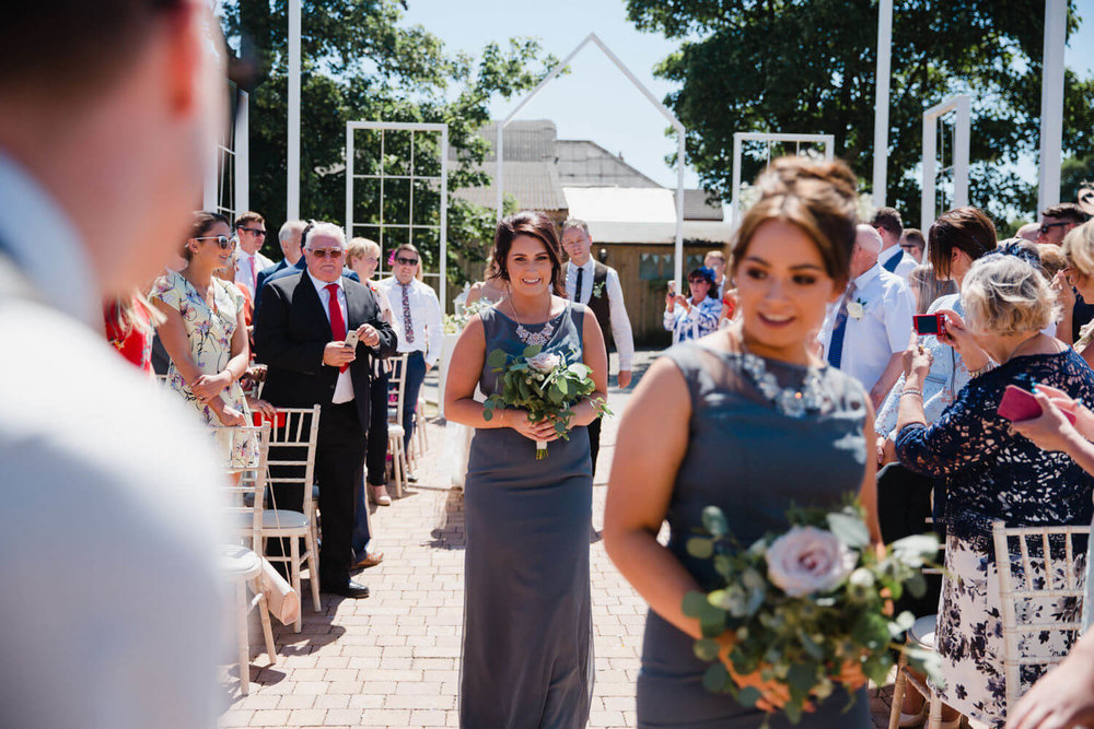 bridesmaid smiling at groom on aisle at alcumlow farm