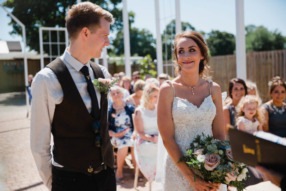 bride smiling at groom at top of aisle