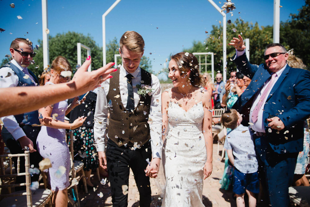 bride laughs with groom while having confetti thrown over them