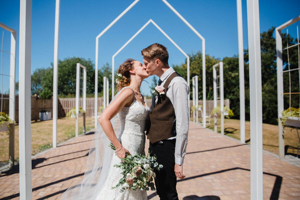 bride and groom kissing under white frame archway