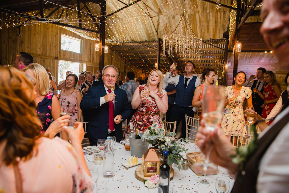 guests laughing at speeches while raising a toast