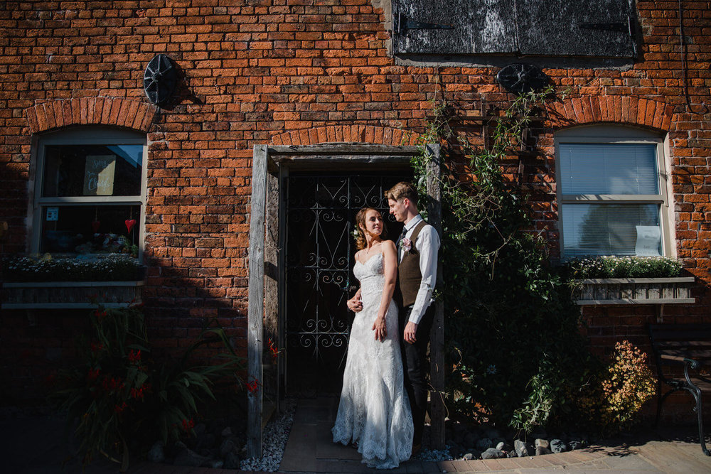 bride and groom holding in sunlight of barn entrance
